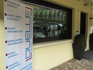 fronte e vetrina della DUELLE SPORT-PROMOTIONS, negozio di premiazioni sportive, gadget aziendlai personalizzati e abbigliamento personalizzato